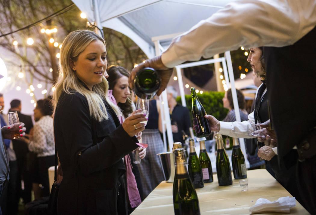 Logan Beierschmitt, of Las Vegas, samples champagne during Bubble-Licious, the UNLVino kickoff ...