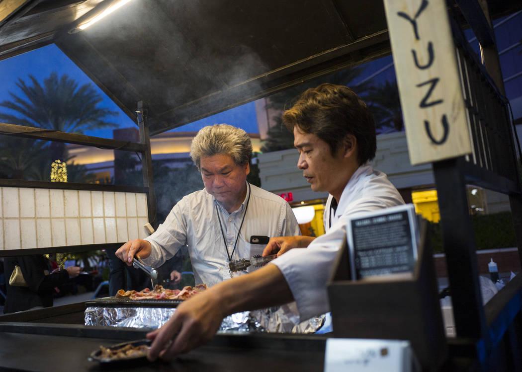 Chef Kaoru ÒAzeÓ Azeuchi of Kaiseki Yuzu prepares grilled pork during UNLVino's Sake ...