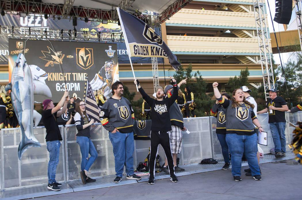 Matt Helfst, center, waves a Golden Knights flag as fans, incluing Alyce Wheeler, right, cheer ...