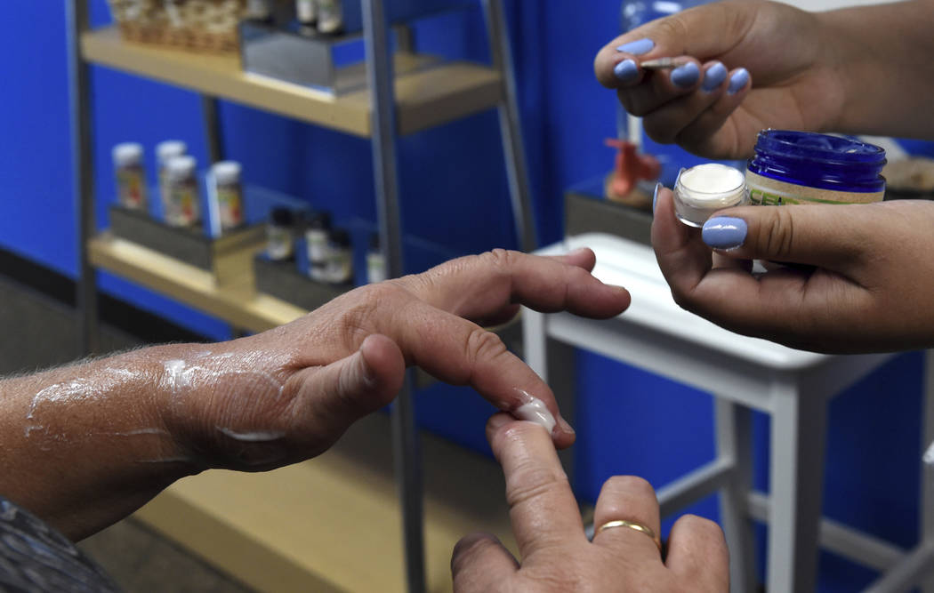 FILE - In this Aug. 29, 2018, file photo, a customer tries a free sample of a pain cream that c ...
