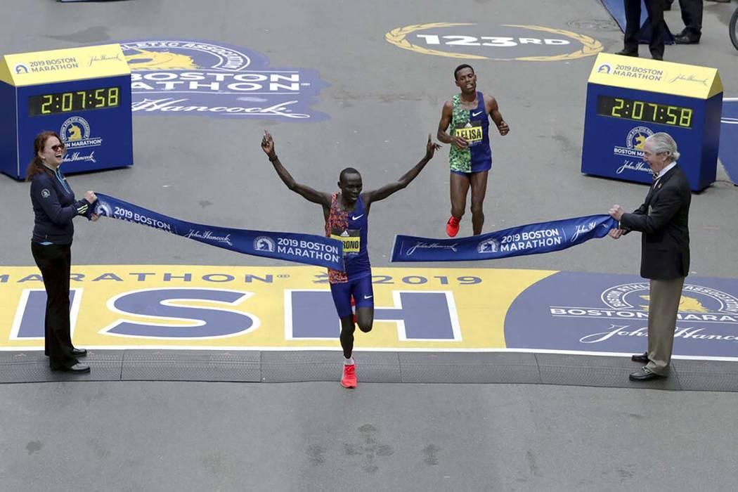 Lawrence Cherono, of Kenya, breaks the tape to win the 123rd Boston Marathon in front of Lelisa ...