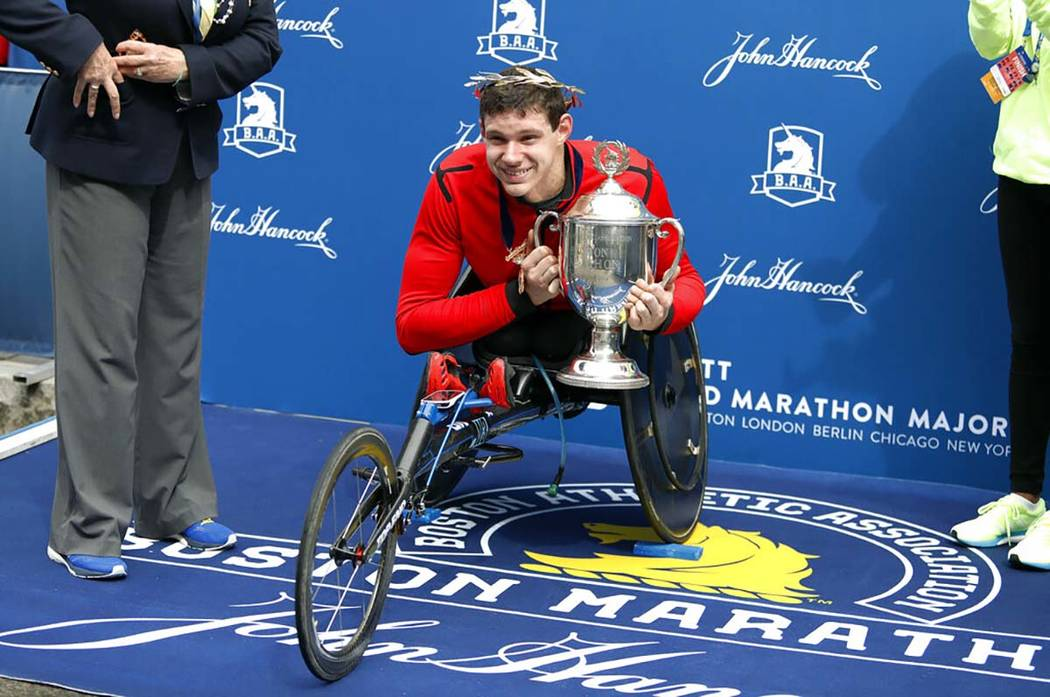 Daniel Romanchuk, of Urbana, Ill., holds the trophy after winning the men's handcycle division ...