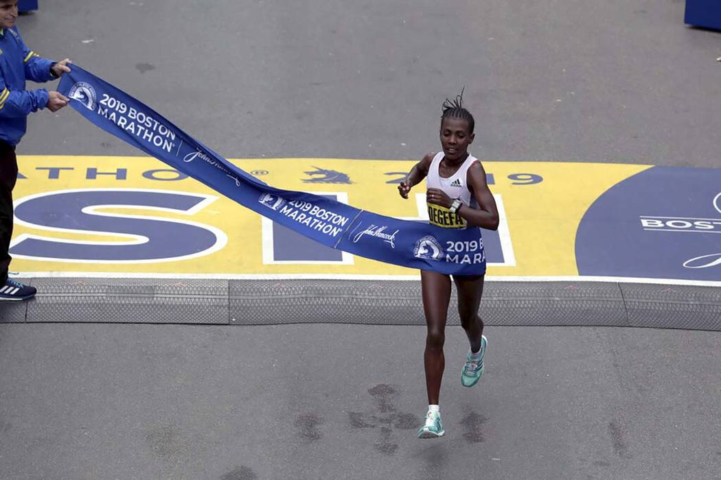 Worknesh Degefa, of Ethiopia, breaks the tape to win the women's division of the 123rd Boston M ...