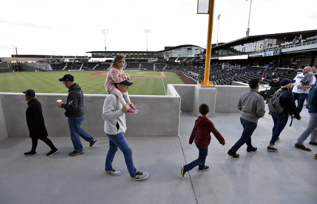 Spectators walk along near left field before the Las Vegas Aviators play the Sacramento River C ...
