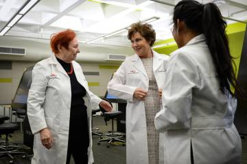 UNLV Medical School Dean Barbara Atkinson, left, gives Sen. Jacky Rosen, D-Nev., a white coat d ...
