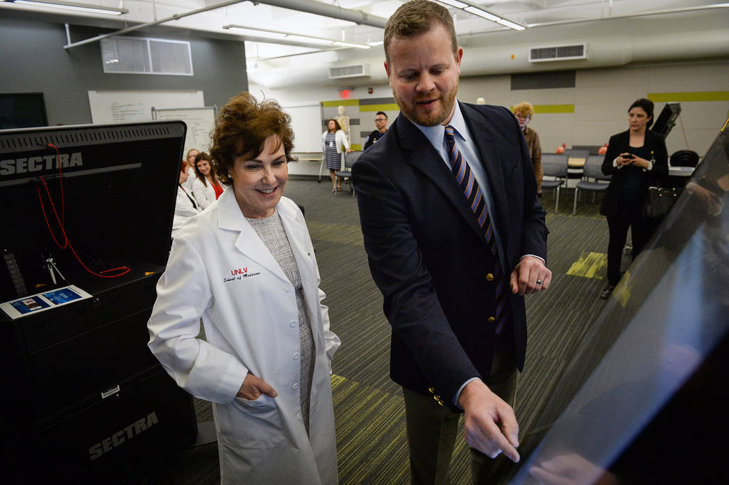 Assistant Dean of Biomedical Science Integration Neil Haycocks, right, shows Sen. Jacky Rosen, ...