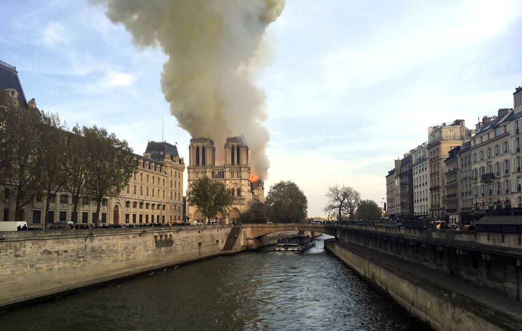 Notre Dame cathedral is burning in Paris, Monday, April 15, 2019. Massive plumes of yellow brow ...