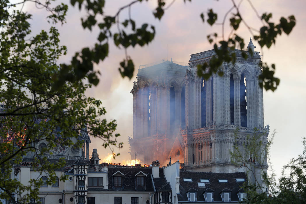 Flames rise from Notre Dame cathedral as it burns in Paris, Monday, April 15, 2019. Massive plu ...