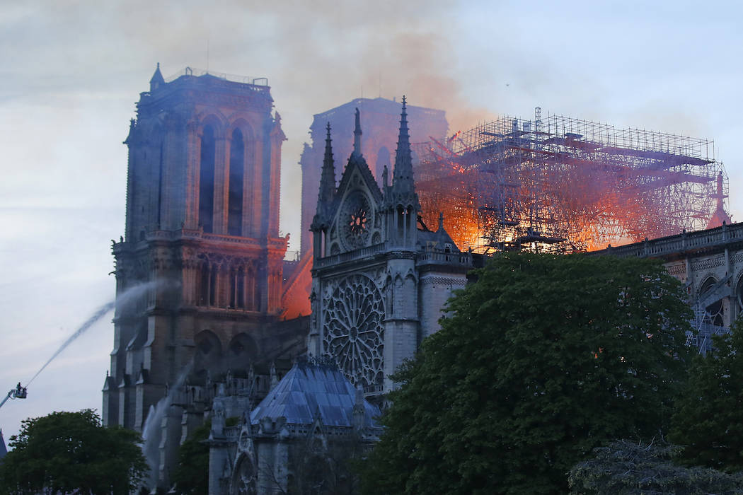 A firefighter tackles the blaze as flames and smoke rise from Notre Dame cathedral as it burns ...