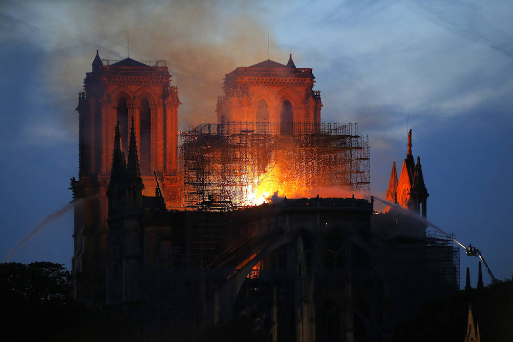 Firefighters tackle the blaze as flames and smoke rise from Notre Dame cathedral as it burns in ...
