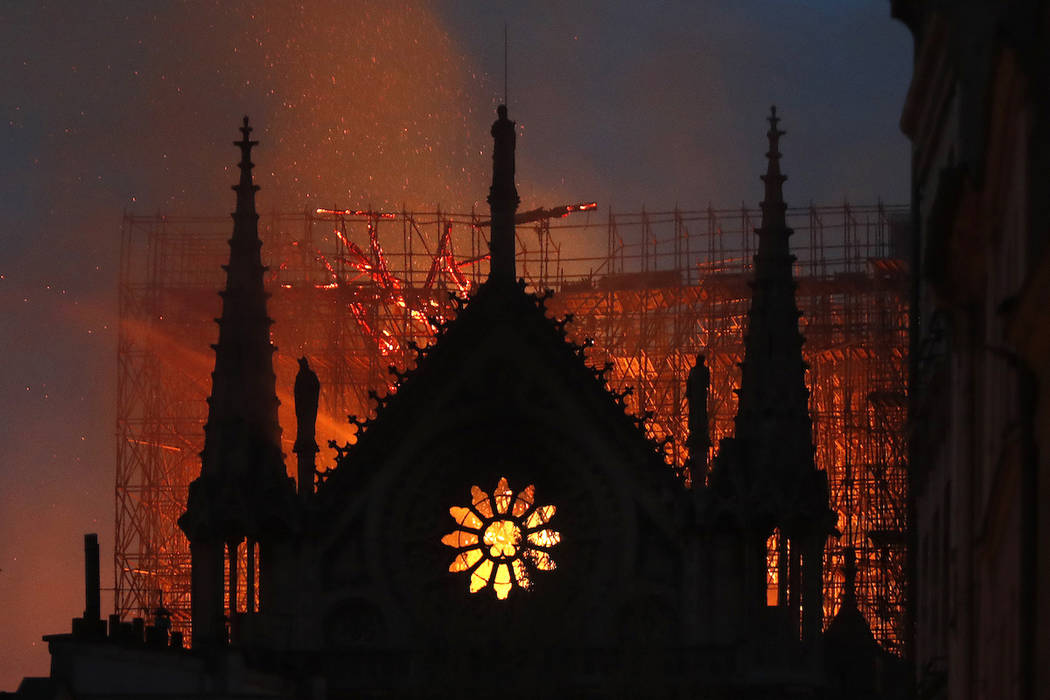 Flames and smoke rise from Notre Dame cathedral as it burns in Paris, Monday, April 15, 2019. M ...