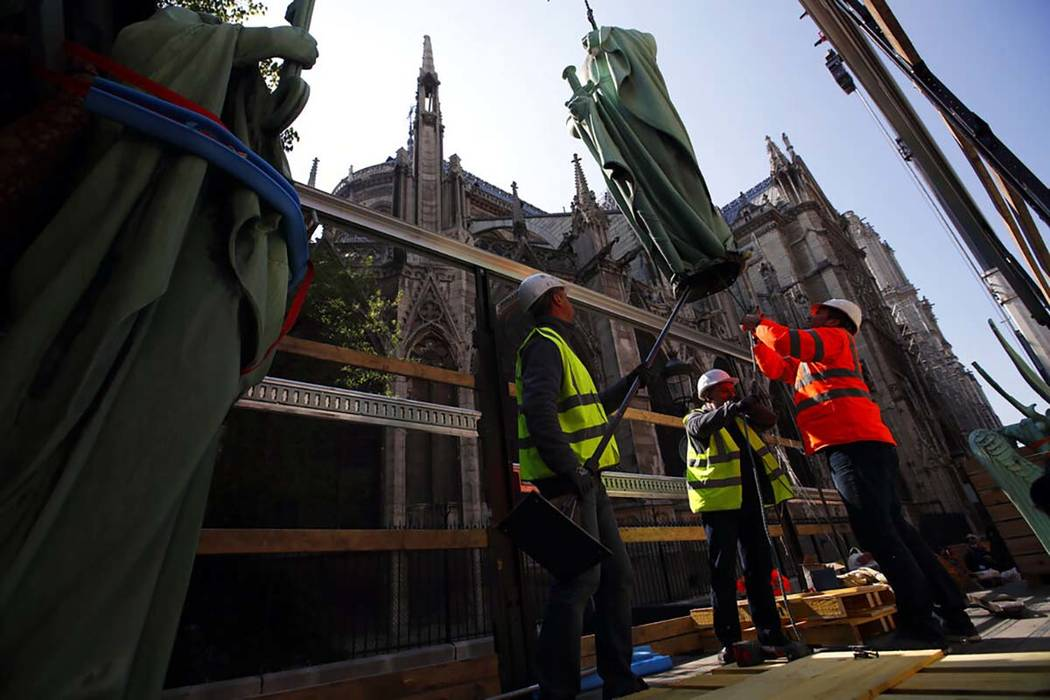 Workers secure a religious statue perched atop Paris' Notre Dame Cathedral as it descends to ea ...