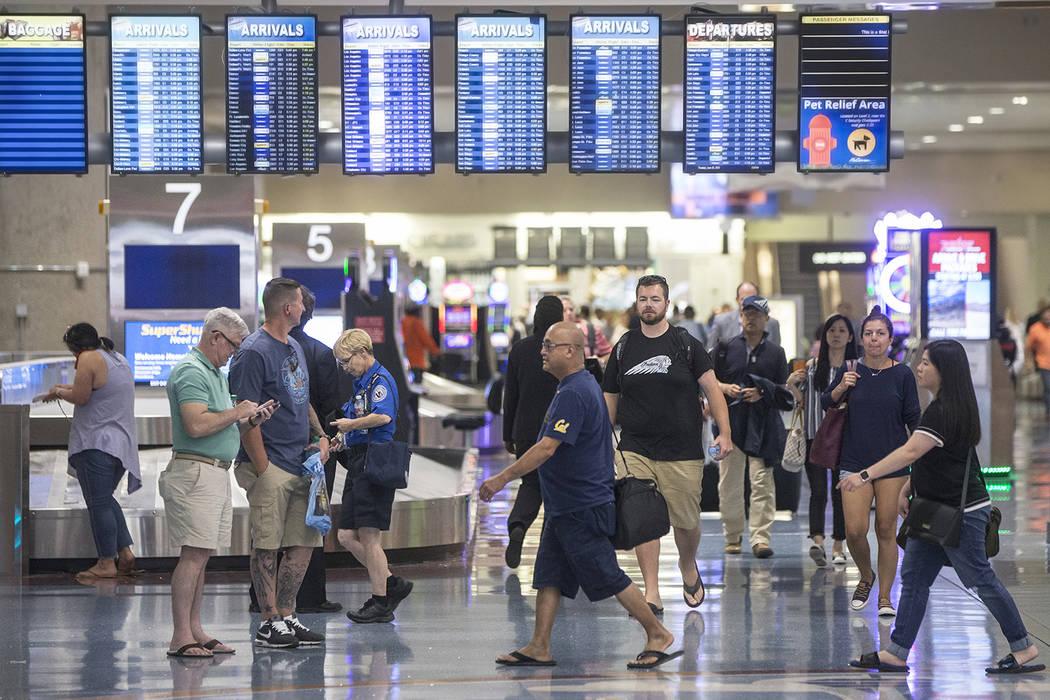 Passengers walk through Terminal 1 baggage claim at McCarran International Airport on Thursday, ...
