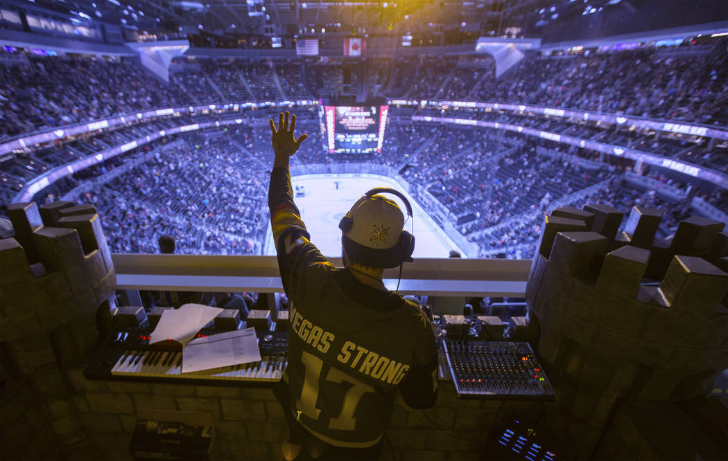Golden Knights music director Jake Wagner waves to the crowd at the end of the first period dur ...