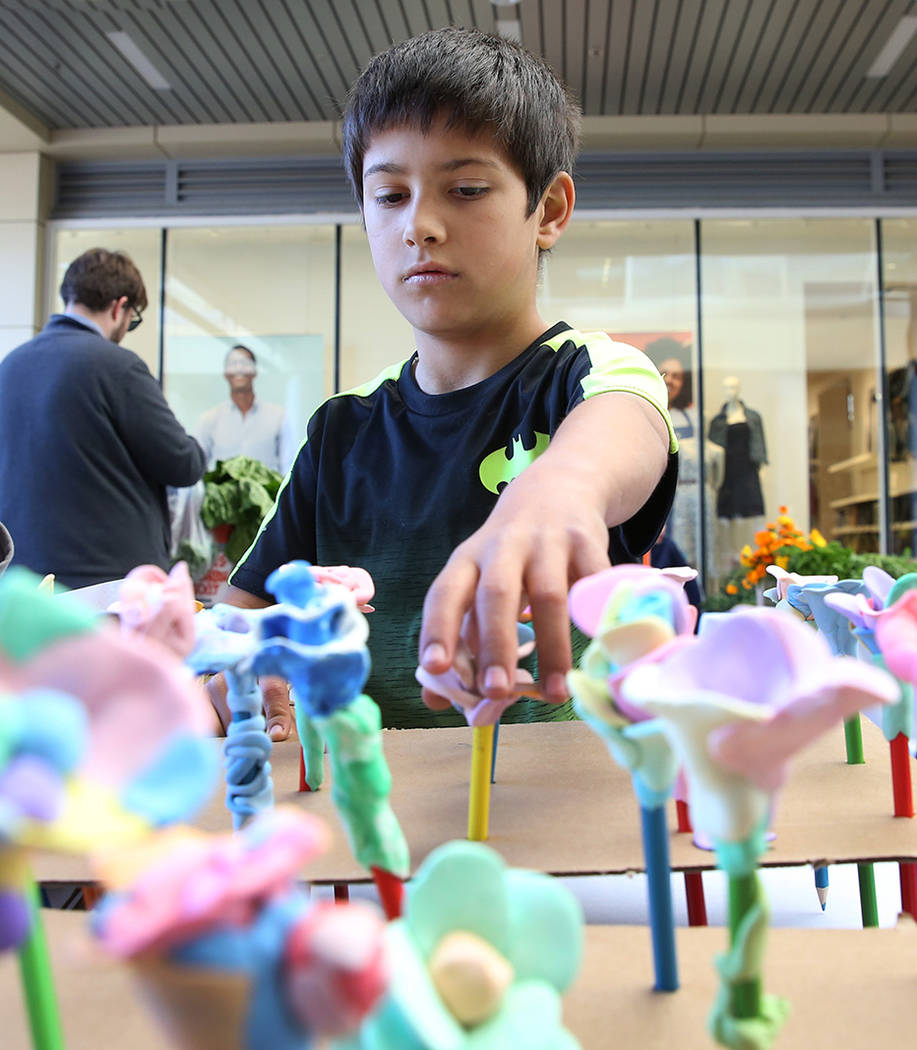 Taylor Elementary School student Richard Estrada, 9, displays flowers made out of clay at Green ...