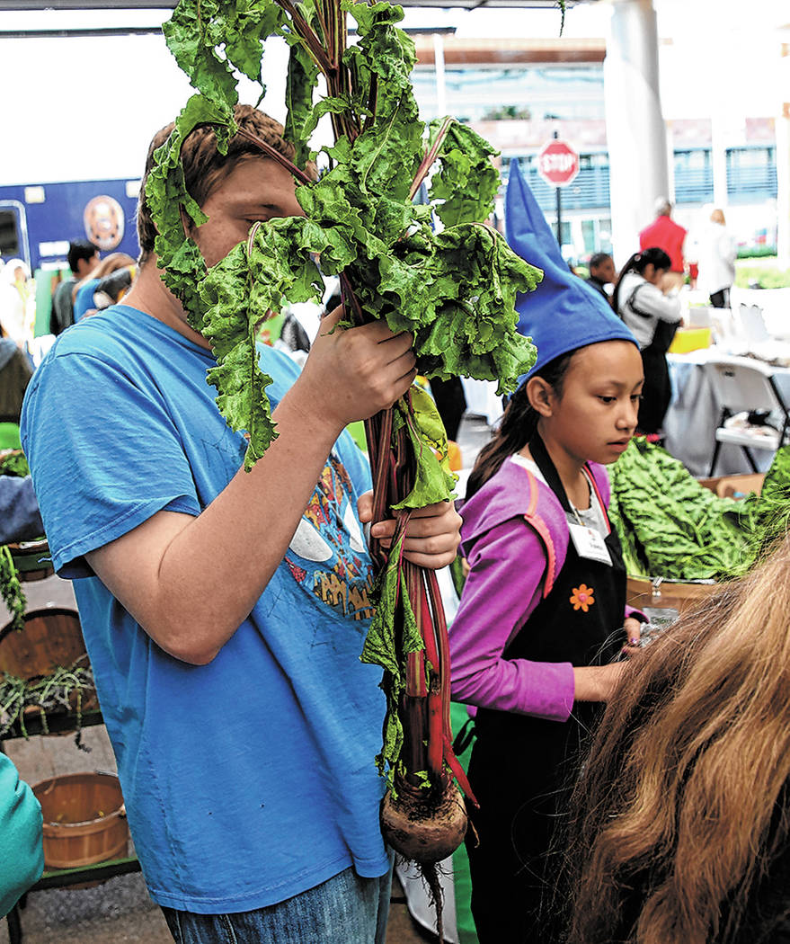Aaron Berkowitz holds his giant beet he bought at Green Our Planet's Giant Student Farmers Mark ...