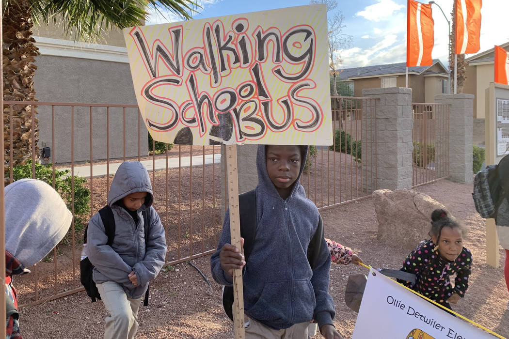 Students walking with Johnson hold signs to let bypassers know they're walking to school. (Mia ...