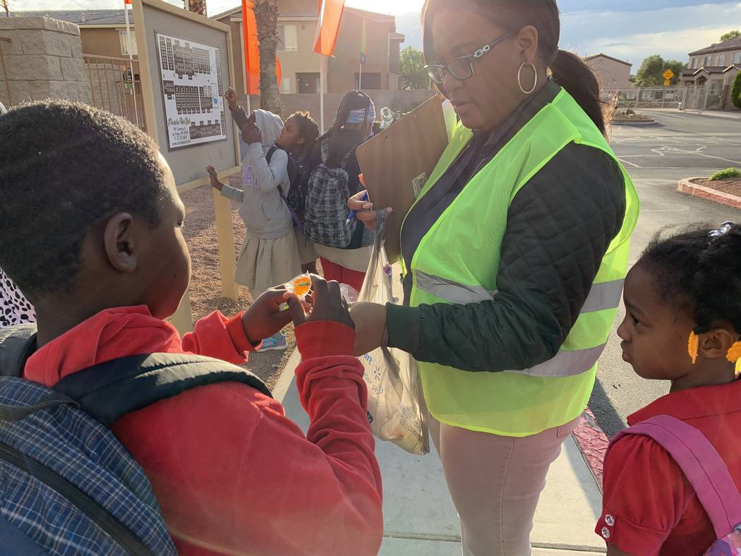Elease Johnson hands out lollipops to students before their walk to Detwiler Elementary. (Mia ...