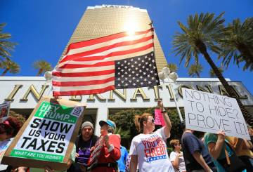 Colleen Brola, center right, holds an upside down American flag during a tax day protest at Tru ...