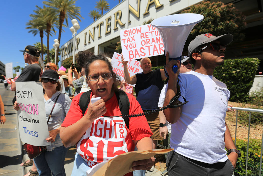 Diana Diaz, with Fight for $15, talks to demonstrators through a megaphone during a tax day pro ...