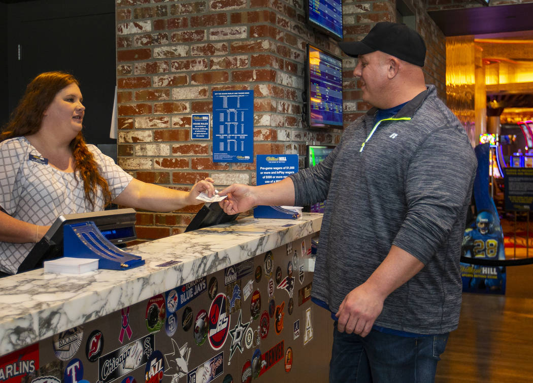 James Adducci of Wisconsin cashes in his $1,190,000 winning payout tickets from the William Hil ...