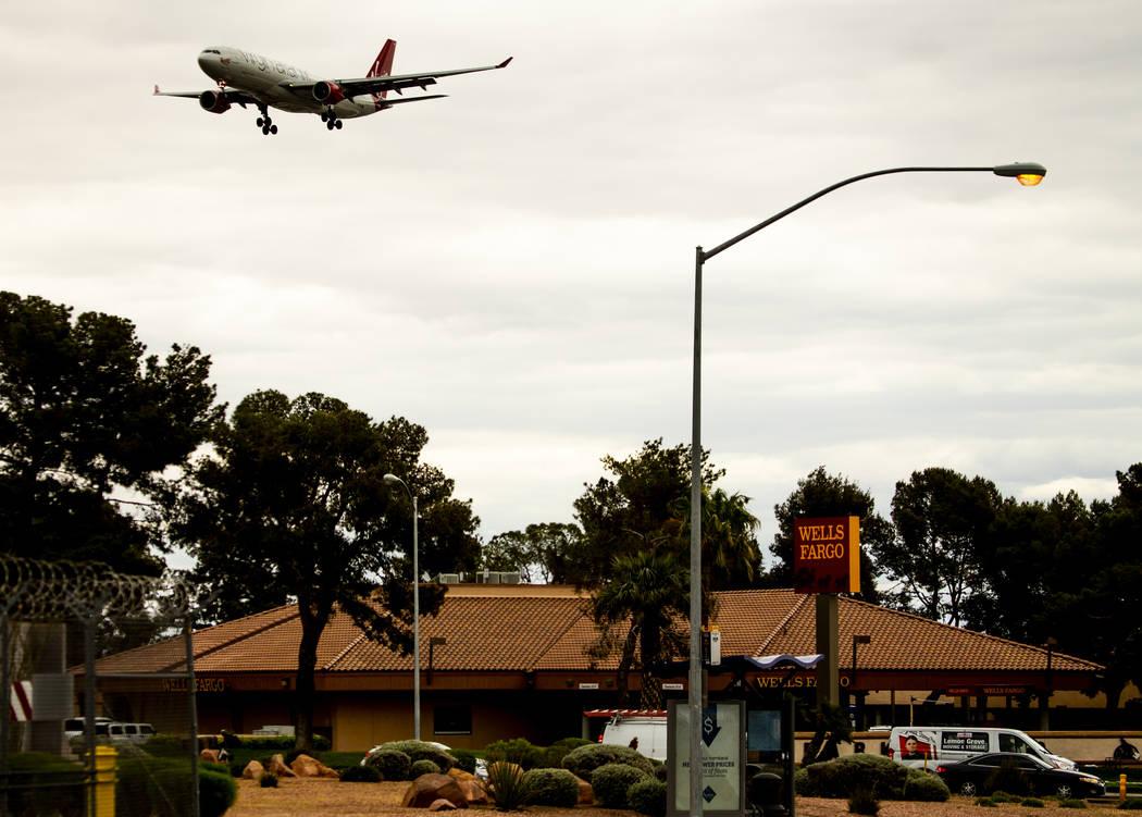 A plane flies low over Wells Fargo Bank near McCarran International Airport on Tuesday, April 1 ...