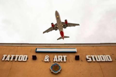 A plane flies low over Lokahi Studios near McCarran International Airport on Tuesday, April 16, ...