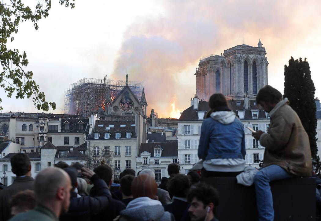 La gente ve cómo las llamas y el humo se elevan desde la catedral de Notre Dame mientras se qu ...
