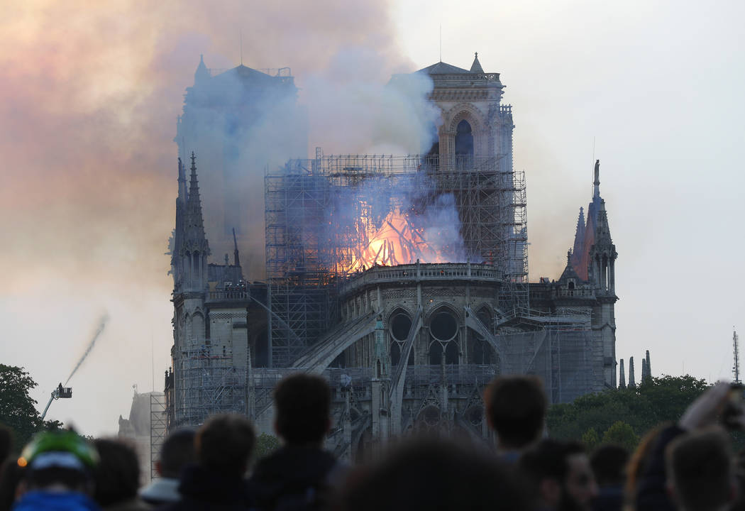 People watch as flames and smoke rise from Notre Dame cathedral as it burns in Paris, Monday, A ...