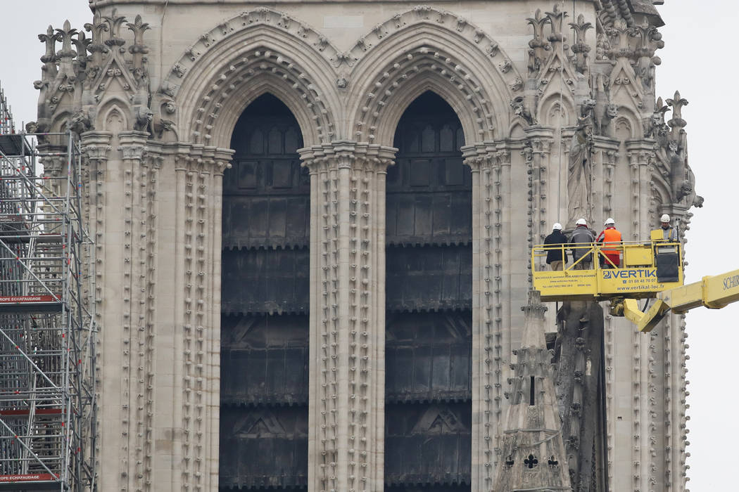 A crane lifts experts as they inspect the damaged Notre Dame cathedral after the fire in Paris, ...