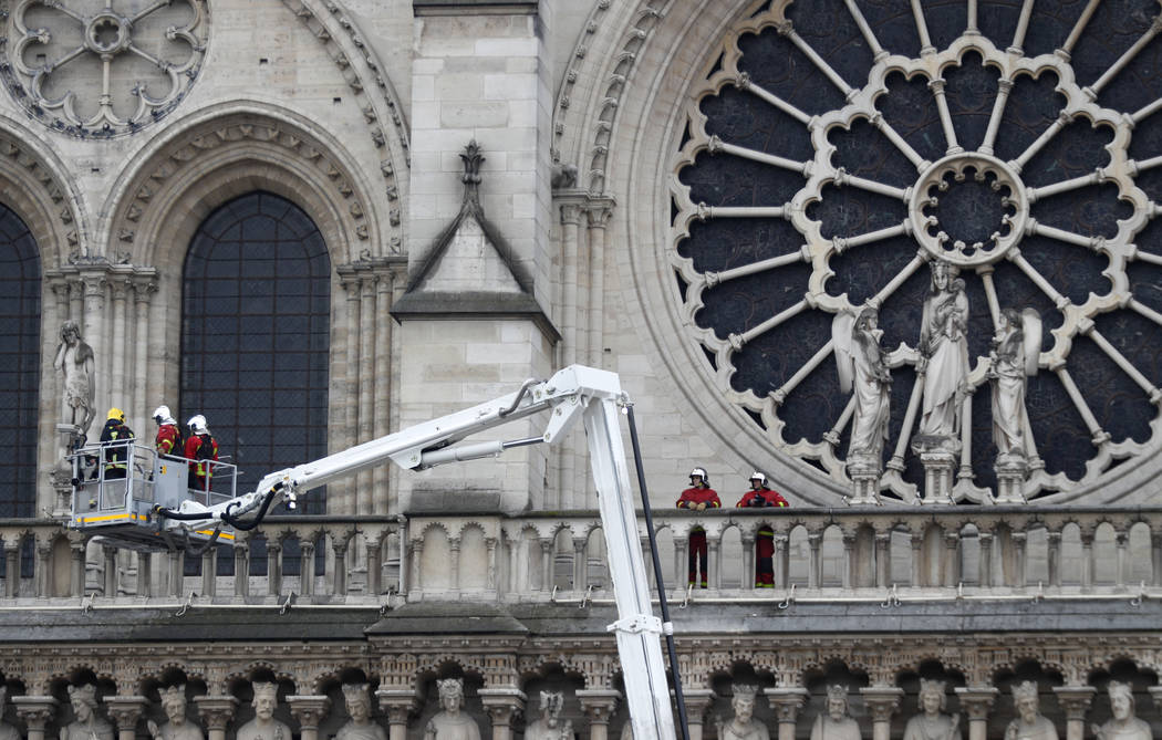 Firefighters work at the facade of Notre Dame cathedral Tuesday April 16, 2019 in Paris. Expert ...