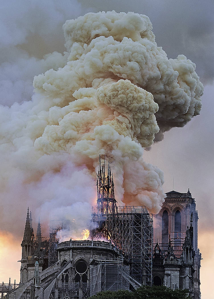 Flames and smoke rise as the spire on Notre Dame cathedral collapses in Paris, Monday, April 15 ...