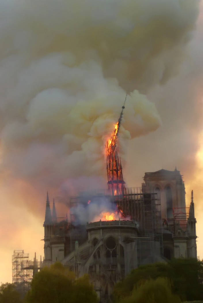 Flames and smoke rise as the spire of Notre Dame cathedral collapses in Paris, Monday, April 15 ...
