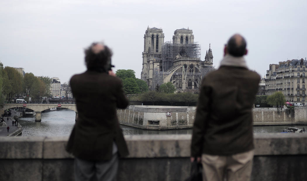 People stop to see and photograph the Notre Dame cathedral after the fire in Paris, Tuesday, Ap ...