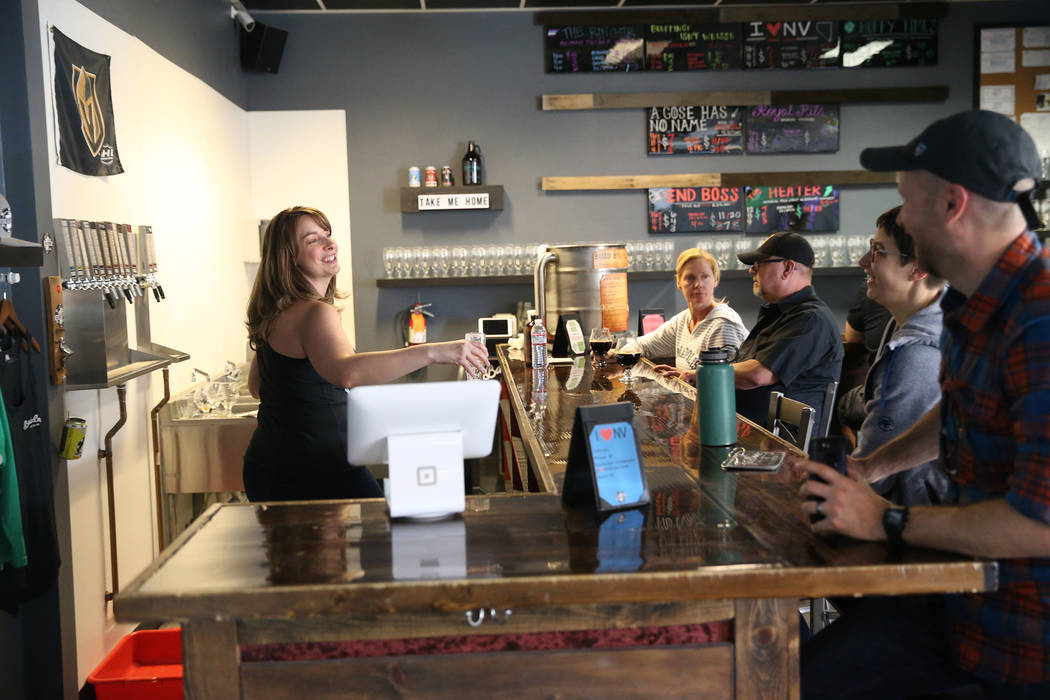 Office manager Amber Barkley, left, speaks with customers at Bad Beat Brewing in Henderson, Sat ...