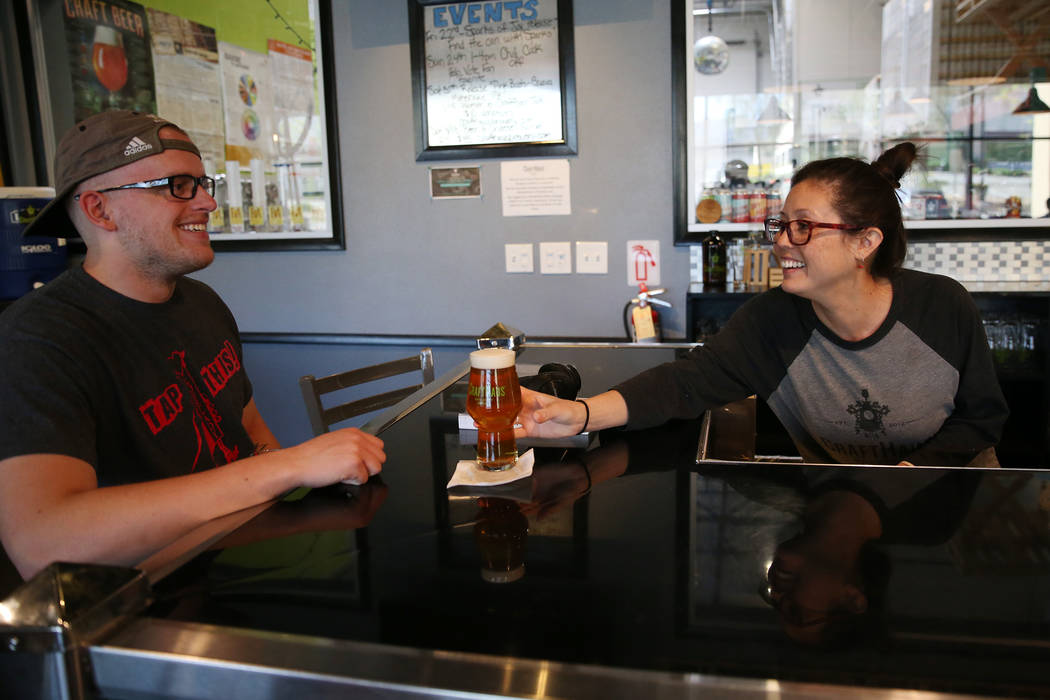 Beertender Chelsie Kesjaral, right, serves a beer for Max Lovelady, at CraftHaus Brewery in Hen ...