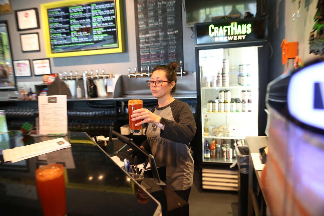 Beertender Chelsie Kesjaral serves a beer at CraftHaus Brewery in Henderson, Saturday, April 13 ...