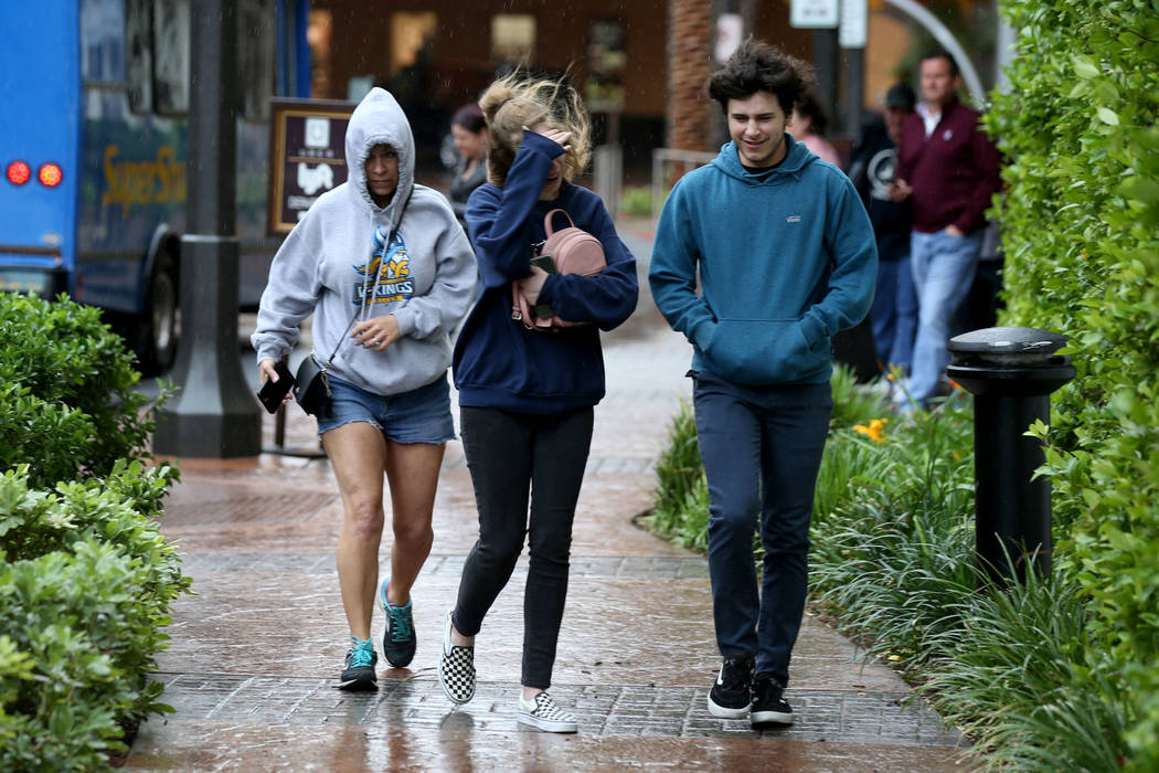 Charli Alu, left, and her children Emilee, 16, and Trevor, 15, make their way through wind and ...
