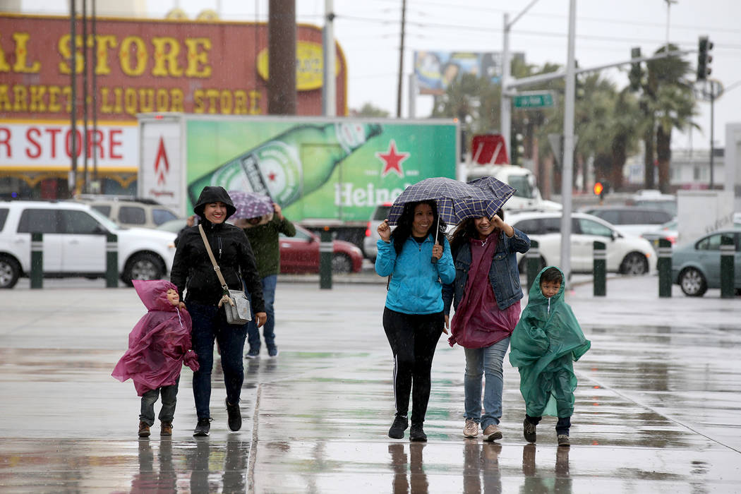 A family walks in wind and rain on Sahara Avenue at Las Vegas Boulevard in Las Vegas Tuesday, A ...