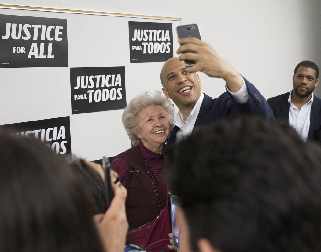 Democratic presidential candidate Sen. Cory Booker, D-N.J., takes photos with supporters at the ...