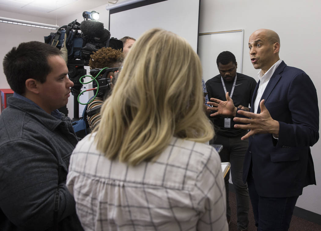 Democratic presidential candidate Sen. Cory Booker, right, D-N.J. takes questions from the medi ...