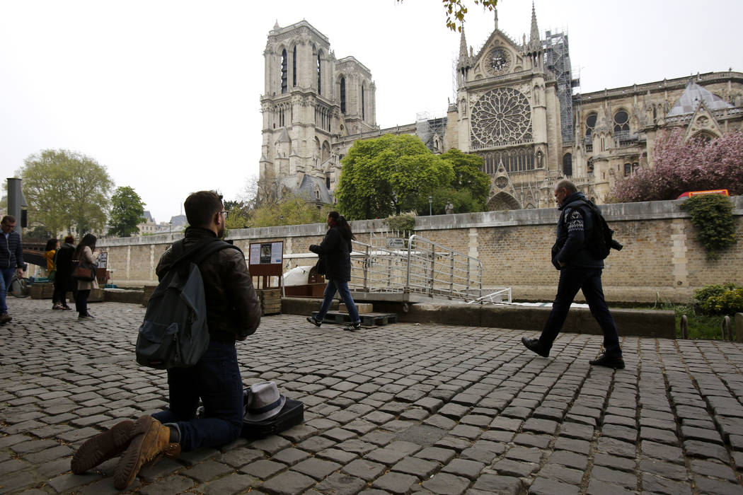 A man kneels as people came to watch and photograph the Notre Dame cathedral after the fire in ...