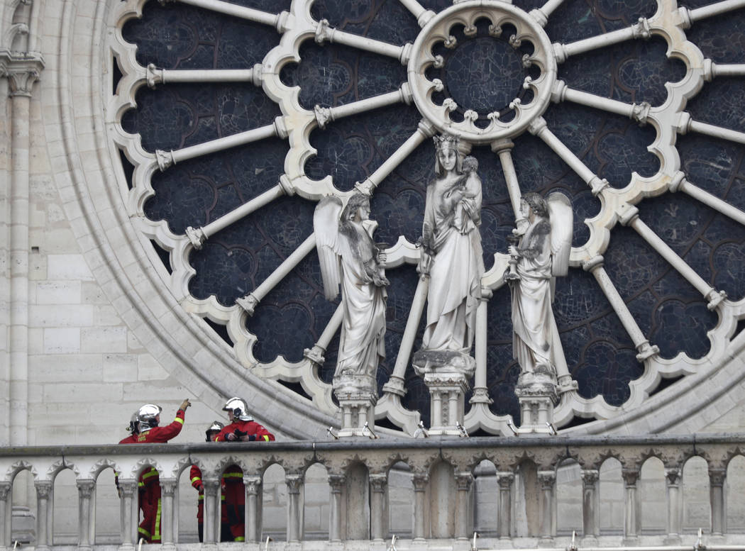 Firefighters talk near the rose window of Notre Dame cathedral Tuesday April 16, 2019 in Paris. ...