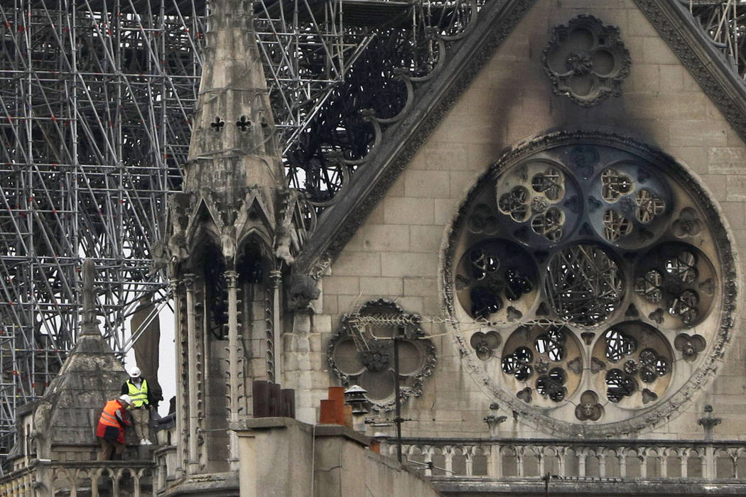 Experts inspect the damaged Notre Dame cathedral after the fire in Paris, Tuesday, April 16, 20 ...