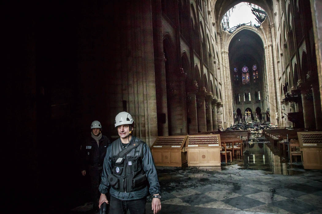 A man walks nside the damaged Notre Dame cathedral in Paris, Tuesday, April 16, 2019. Firefight ...