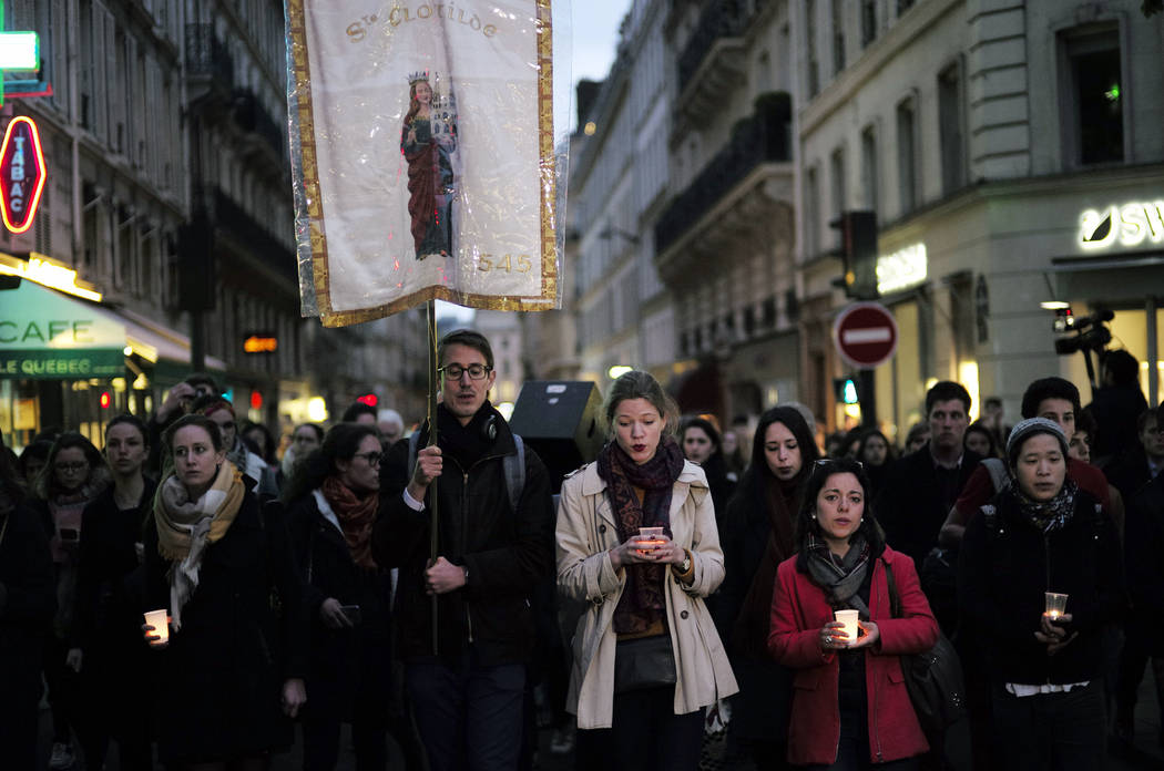 People walk toward the Notre Dame Cathedral to attend a vigil, in Paris, Tuesday April 16, 2019 ...