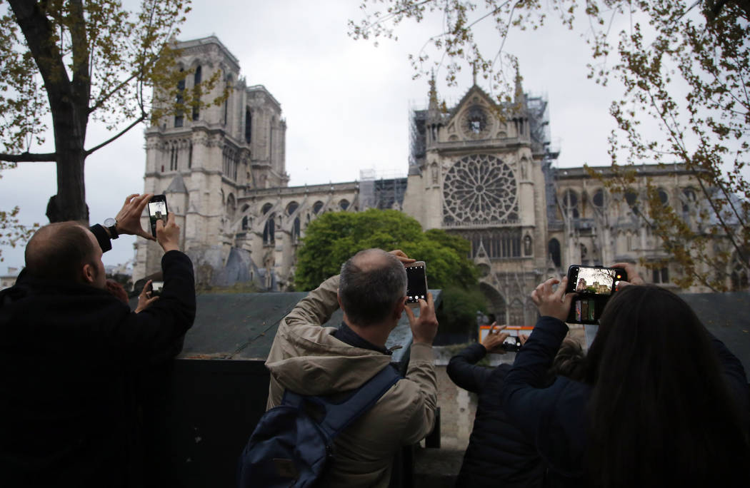 People take photos of the Notre Dame Cathedral in Paris, Tuesday April 16, 2019. Firefighters d ...