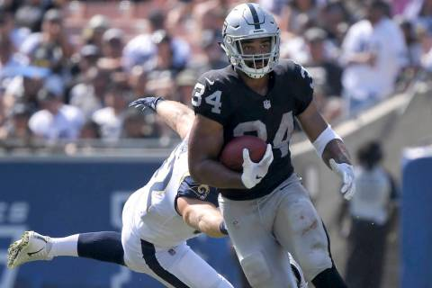 Oakland Raiders running back Chris Warren runs past Los Angeles Rams defensive end Brian Womac ...