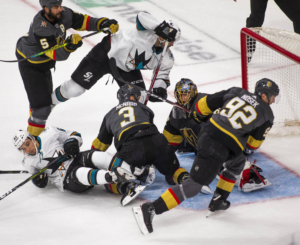Golden Knights goaltender Marc-Andre Fleury (29) makes a stop amongst teammates and San Jose Sh ...
