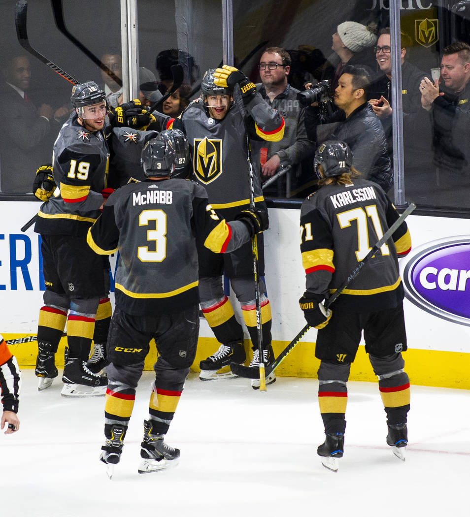 Golden Knights players celebrate a goal by defenseman Shea Theodore (27) during the first perio ...